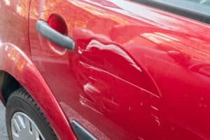 car with dented door and scratches