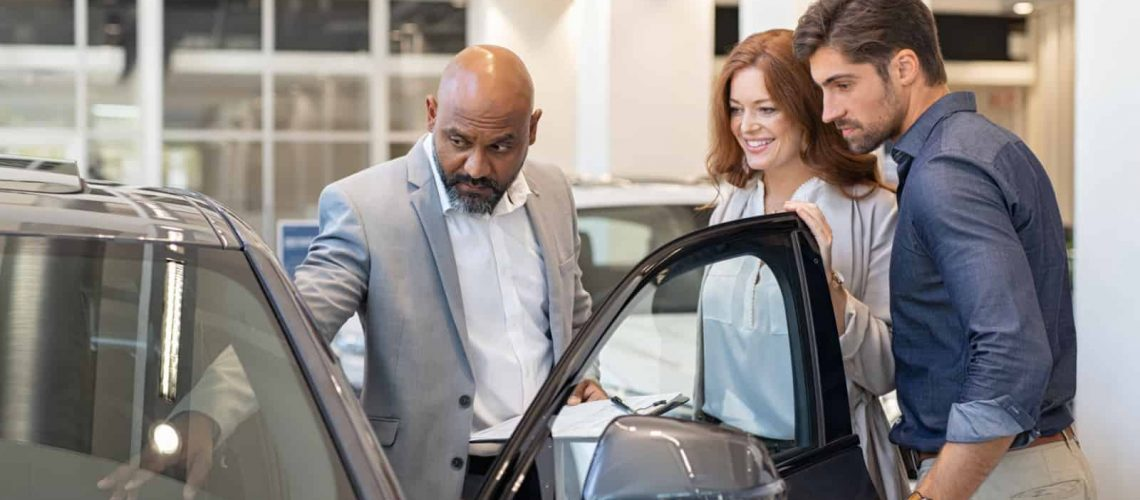 Salesman showing car features to a couple